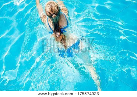 Top view image of young girl swimming in pool. Summer vacations background