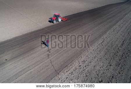 Aerial image of tractor harrowing soil and engineer with laptop in field in springtime shoot from drone