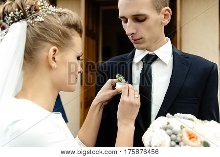 Stylish Gorgeous Bride Putting On  Boutonniere On Elegant Groom At Church Ceremony