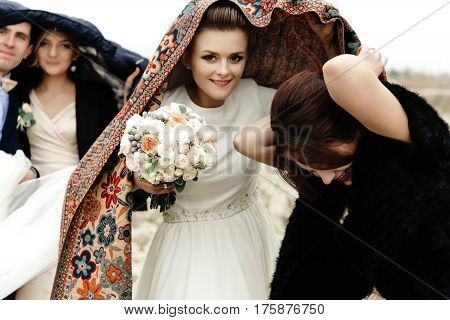 Happy Bride With Bouquet Under Scarf With Groomsmen And Bridesmaids Having Fun, Rain Outdoors, Hilar