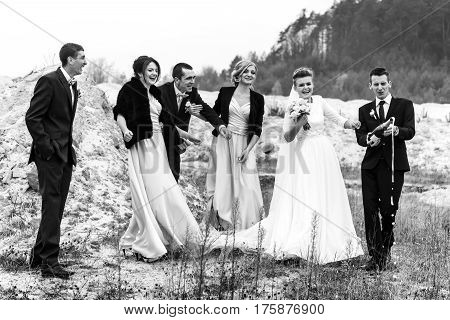 Bride And Groom With Happy Groomsmen And Bridesmaids Having Fun And Laughing And Popping Champagne,