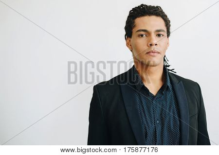 Happy young businessman in black suite and blue shirt standing over white background. Portrait of a handsome mulatto boy. Color