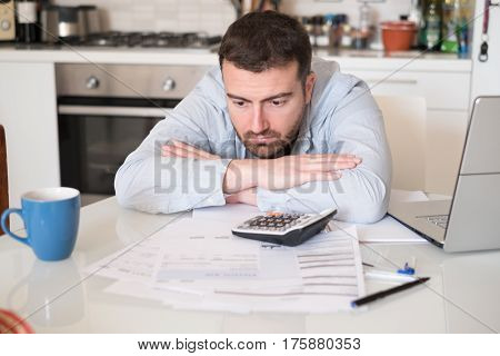 Frustrated Man Calculating Bills And Taxes