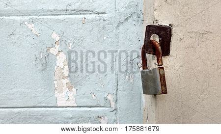 The rusty key lock hangs on a gate.