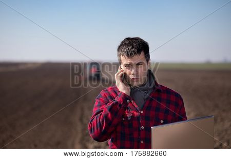 Famer With Laptop And Cell Phone In Field