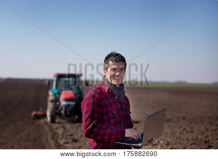 Famer With Laptop And Tractor In Field