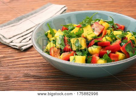 Mango salad with pepper and parsley in a bowl. Healthy low fat detox eating concept.