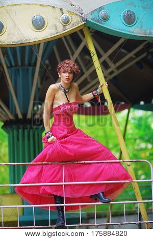 Extravagant portrait of young attractive model in red dress shooting for advertising fashion shop on old abandoned carousel in a city Park.