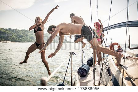 Fiends having fun on a sail boat and jump in the water