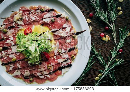 Salad of veal carpaccio in a white plate close-up on a wooden table