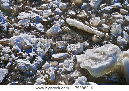 Beautiful natural background. Pieces of ice frozen in the clear river water on a bright Sunny day