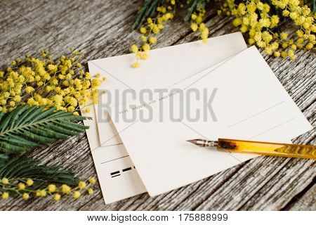 Vintage post cards mock up with yellow flowers mimosas and vintage pen ink on grey wooden background. Overhead view. Flat lay, top view, moke up