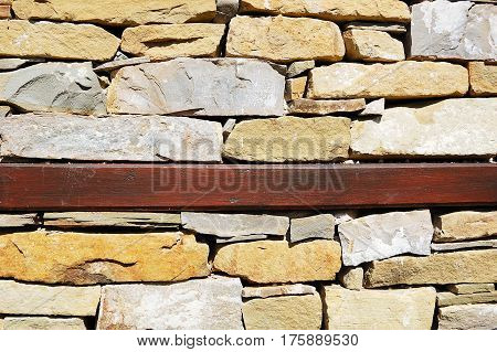 Wall of a traditinal bulgarian house with wooden beam between layers of stones