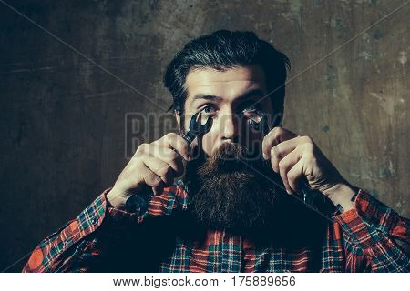 Surprised Bearded Man Fastening Eyes With Wrenches