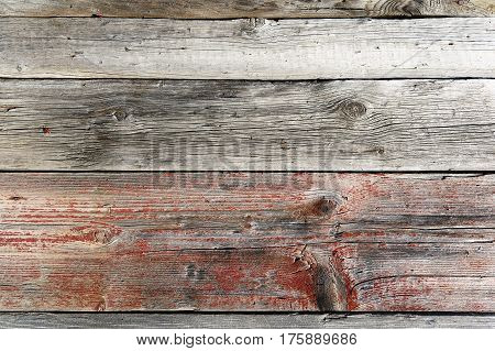 A fragment of a fence built of unpainted weathered wooden boards