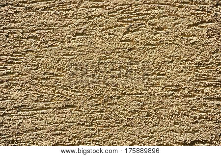 Fragment of a wall covered with modern grainy sandy-yellow stucco