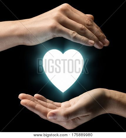 Isolated image of two hands on black background. Heart icon in the center as a symbol of love and care. Concept of care of love and care.