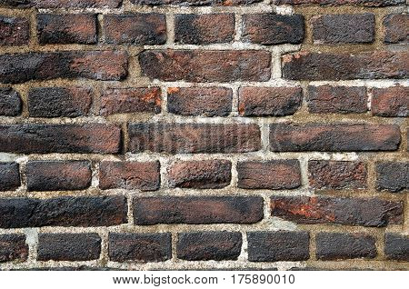 Rough aged wall made of flamed bricks