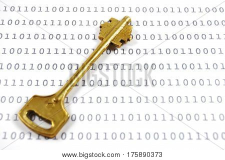 Golden key on a sheet with binary encrypted data. Encryption concept.