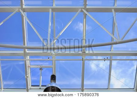 Roof made of glass and metal with window motor and lamp against blue sky background