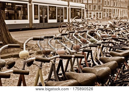 A lot of colored bicycles at the bike rental station on a rainy day in Amsterdam. Sepia toned image.