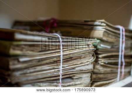 Paper files in a folder is a old documents or old letter it's a age-old and ancient archiving by stacking up in a documents paper shelf messy order poster