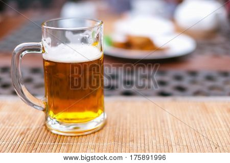 beer mug with beer on a table outside