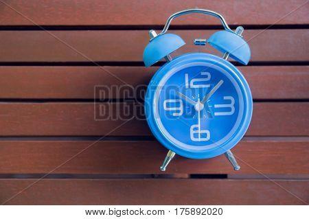 Blue alarm clock on wood background close up blue alarm clock