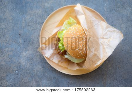 Hamburger with fresh vegetables and meat on wood dish