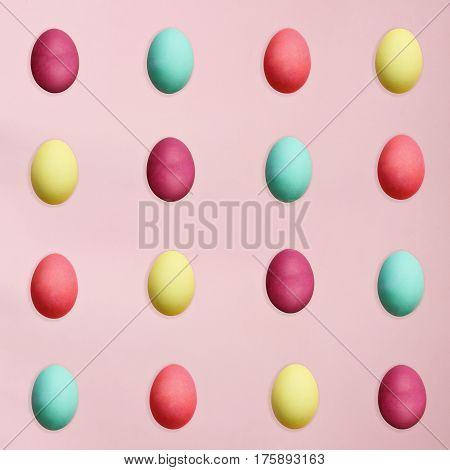 Rows of colorful Easter eggs isolated over a pink background. Flat lay style.