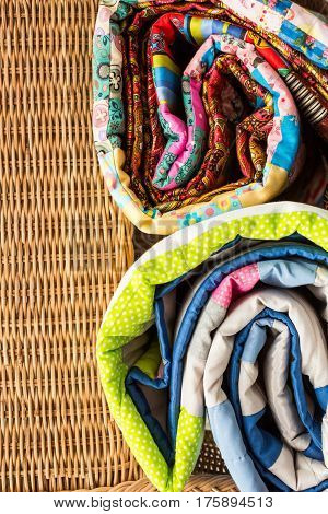 the two colored scrappy blankets rolled by on a wicker country chair close up. beautiful patchwork quilt with a flower pattern.