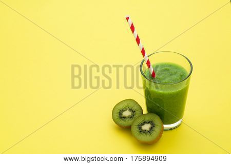 Healthy fresh kiwi smoothie in glass on a yellow background