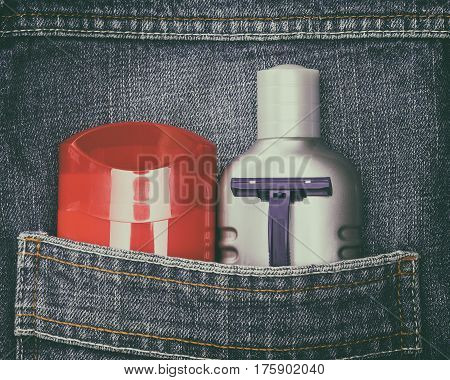 Mens cosmetics. Antiperspirant deodorant, aftershave lotion and disposable razor in jeans pocket. Toiletry and cosmetic travel kit. Toned image