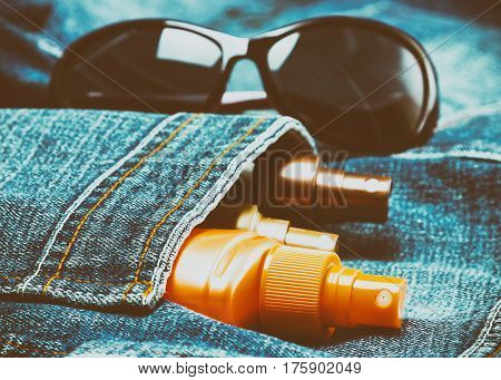 Sunscreen cosmetic products in jeans pocket with sunglasses. Skin care cosmetics containing sun protection factor