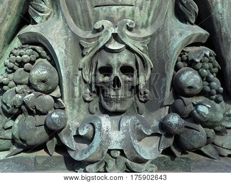 Beautiful skull in bronze patinated by time and elements. Photographed outside on an abandoned grave. Natural light, colors and patina. Pere Lachaise Cemetery, Paris, France.