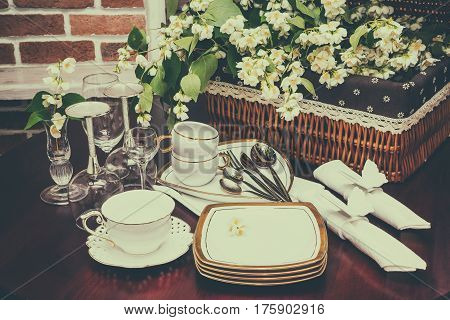 set of dishes glasses mug and jasmine flowers on a background of wicker baskets. interior wooden table. close-up