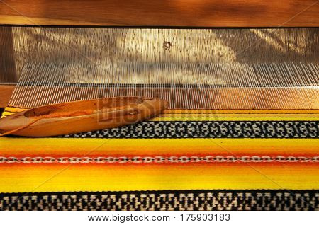 Crafts. Hand loom with many colorful woolen threads.
