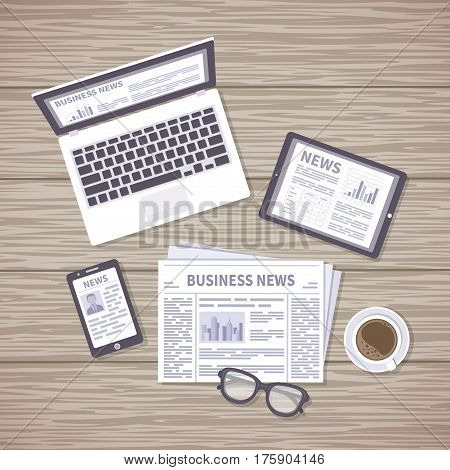 News concept. Daily information from different resources on the screens of devices and in the paper. News on laptop, tablet, phone, newspaper with coffee and glasses on a wooden desk. View from above
