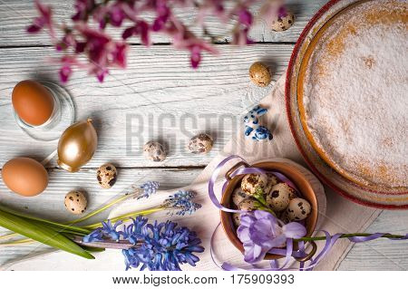 German Easter cake, eggs, flowers, ribbons on the table copy space horizontal