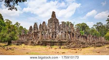 Bayon temple in Angkor Thom. Mysterious Angkor Thom nestled among rainforest in Siem Reap, Cambodia. Enigmatic Angkor Thom is a popular tourist attraction.