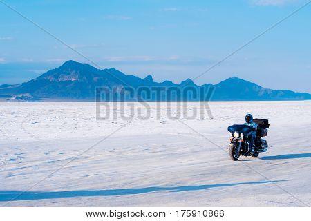 Biker driving across Bonneville Salt Flats in Utah, USA