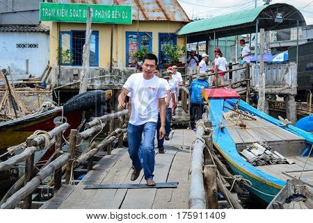 People Walking On Wooden Bridge At The Jetty