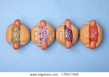 four different hotdogs with pesto tomato onion bbq sauce isolated on blue background