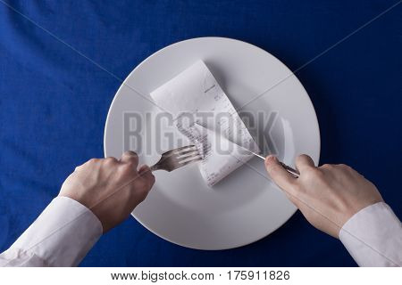 male hands cutting restaurant bill receipt by knife and fork on white dish on blue tablecloth