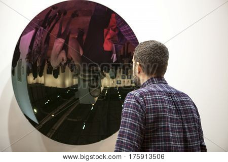 Madrid Spain - Feb 26 2017. The contemporary art fair ARCO opens in Madrid. Visitor observing work made with mirror