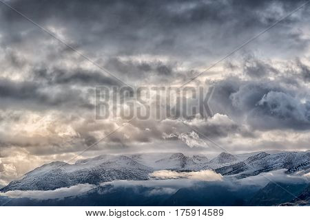 Stormy sky over snow caped mountain range in Norway
