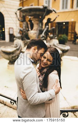 Young Couple In Love Hugging Near The Fountains In Rome