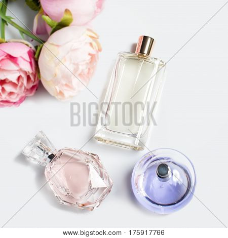 Perfume bottles with flowers on light background. Perfumery, cosmetics, fragrance collection. Flat lay.
