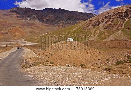 Two Motorcyclists on the Winding Road in the High-Altitude Mountain Desert in the Himalayas, Ladakh, Northern India