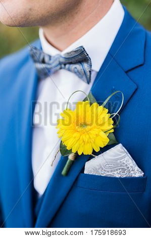Groom wearing blue suit with yellow flower as acessorie